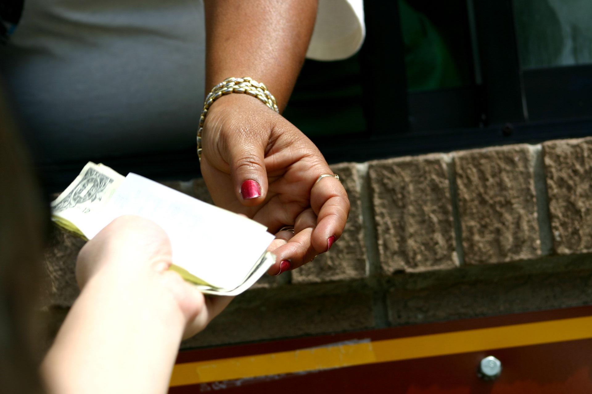 hands exchanging money at a drive-thru window