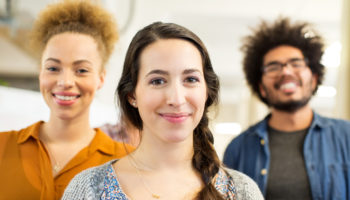 Portrait of confident young woman with colleagues in background at office
