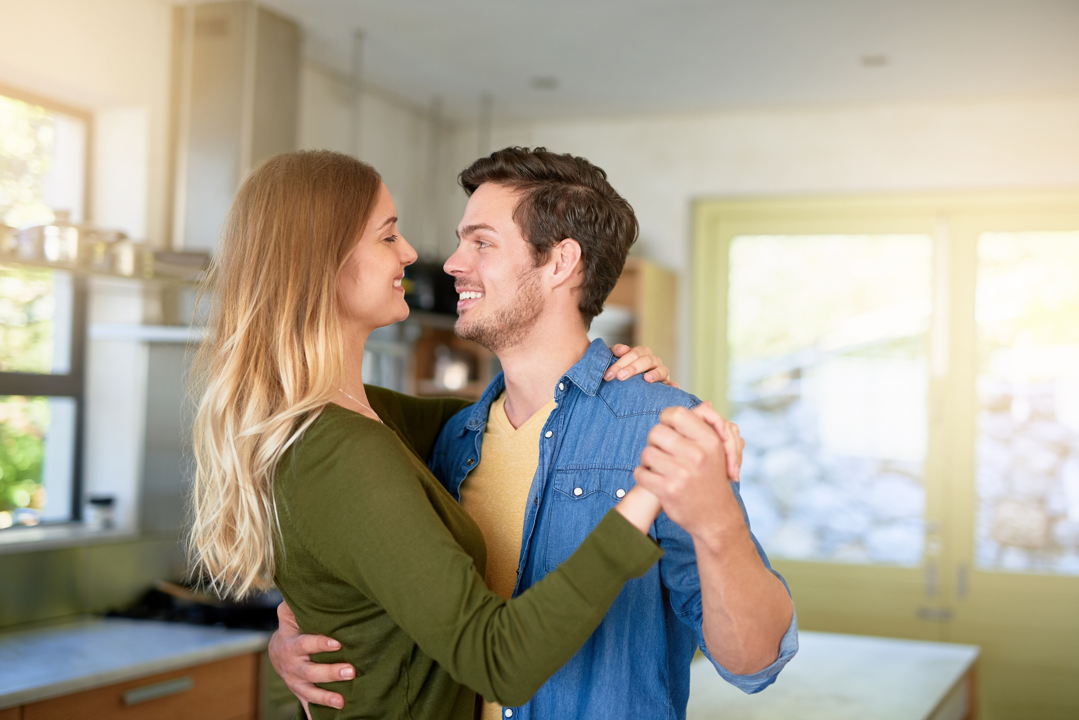 Shot of an affectionate young couple dancing hand in hand together in their kitchen