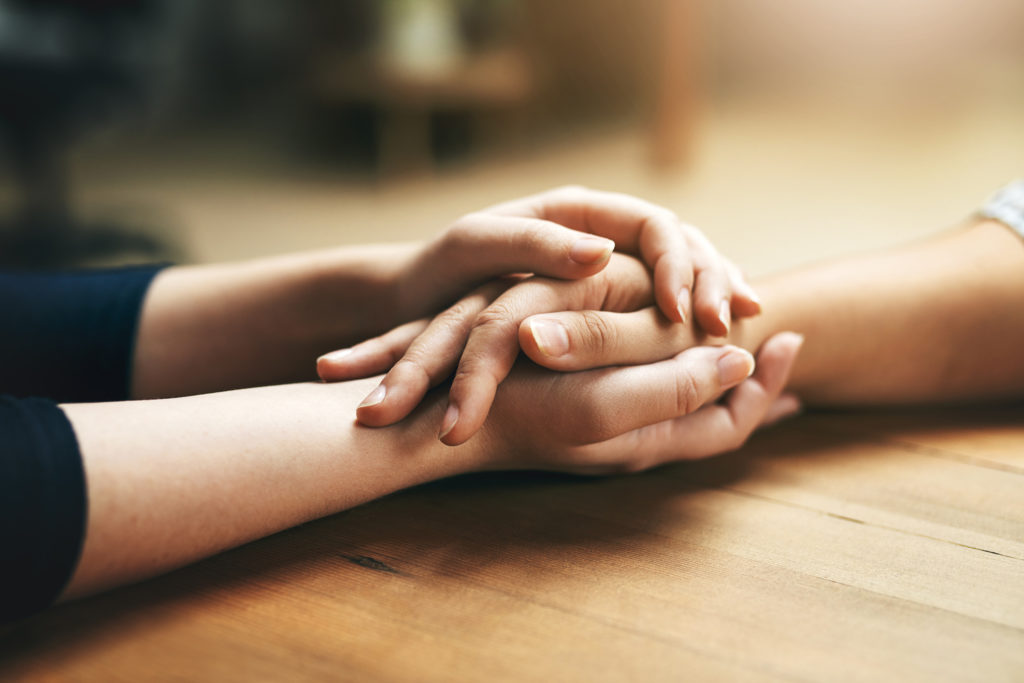 Closeup shot of two unidentifiable people holding hands in comfort