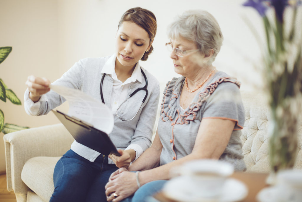 Latin nurse with a stethoscope around her neck is consulting with a senior lady on a sofa. As she speaks, she is showing and sharing the examination results to her patient.