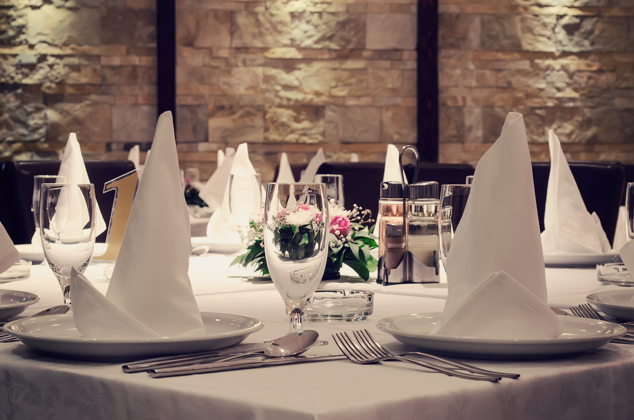 Photo of a restaurant table set for dinner, wedding day, celebrations or similar events.
