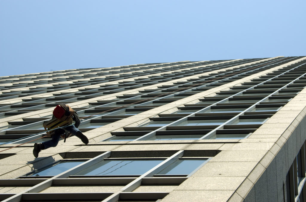 A man hanging in a harness and fixing windows on a tall building