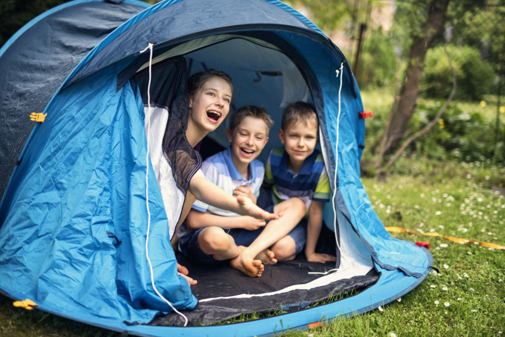 Kids aged 8 and 12 are laughing happily sitting inside of blue tent - playing camping in garden. Kids are surprised by summer rain. Nikon D850