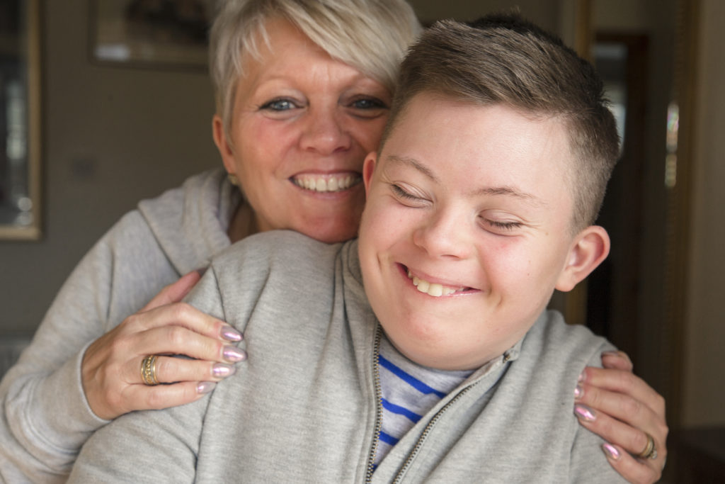 A boy with down syndrome spends quality time with his mother.