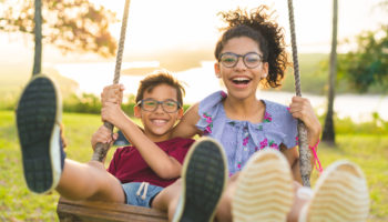 Happy children swinging and smiling at golden sunset