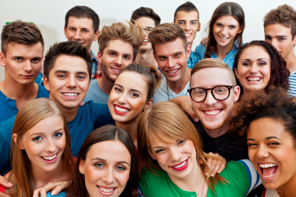 Large group of young adult people laughing at the camera. Close up of faces.
