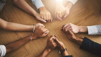 Closeup shot of a group of businesspeople sitting together at a table and holding hands