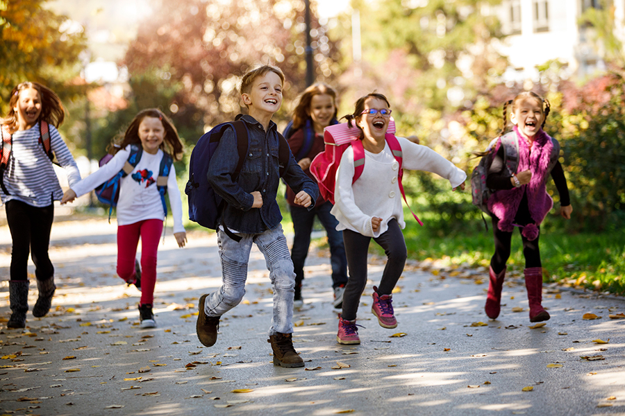 Happy schoolchildren running in a park