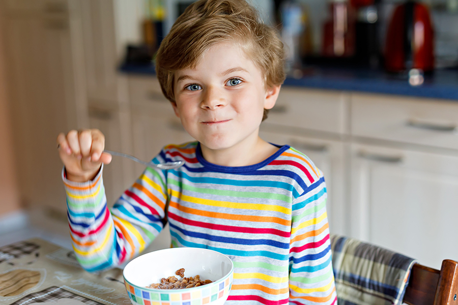 A cute kid eating cereal