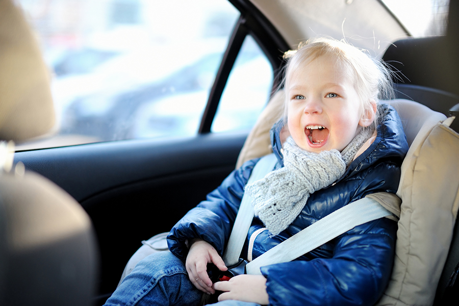 Happy little girl riding in a car seat