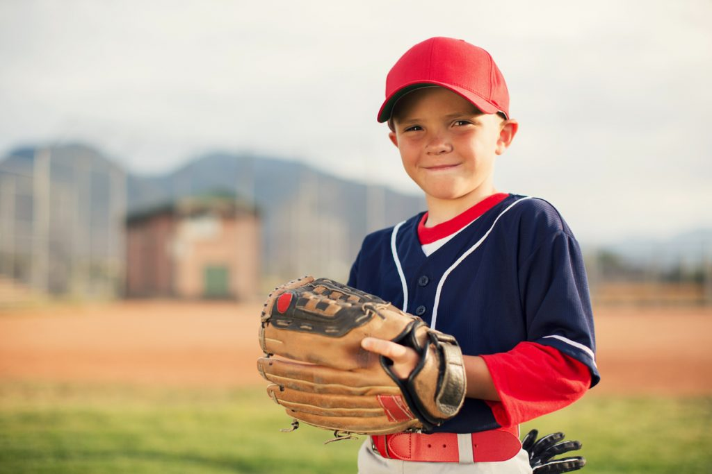 A young Little League baseball player is wearing a baseball uniform and holding his baseball glove while smiling and looking at the camera. He is playing on a warm summer day in Utah, USA.