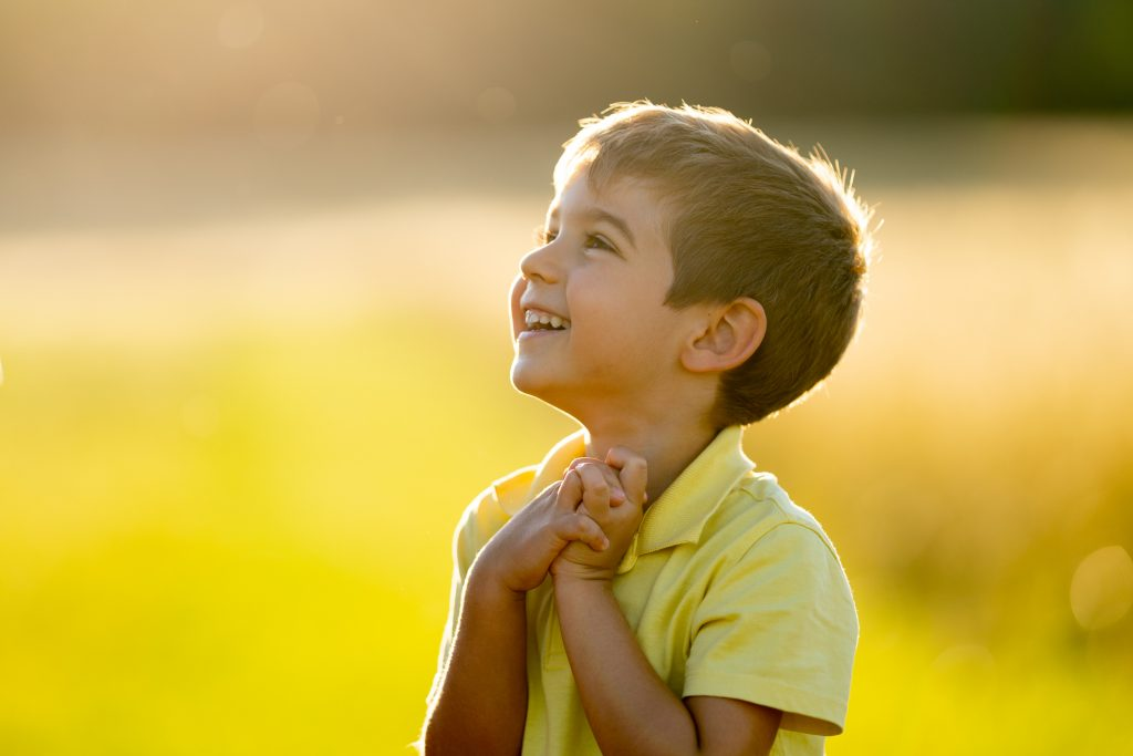4 year old boy laughing full of joy looking excited and grateful