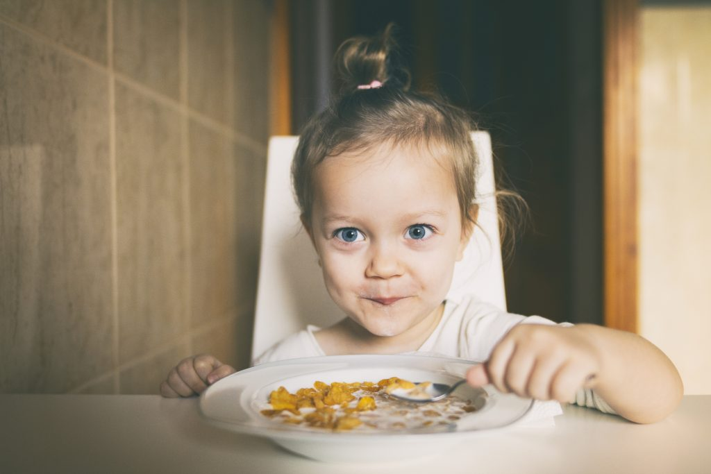 Three years old girl sitting at the table in the kitchen and eating corn flakes with milk.Three years old girl sitting at the table in the kitchen and eating corn flakes with milk.