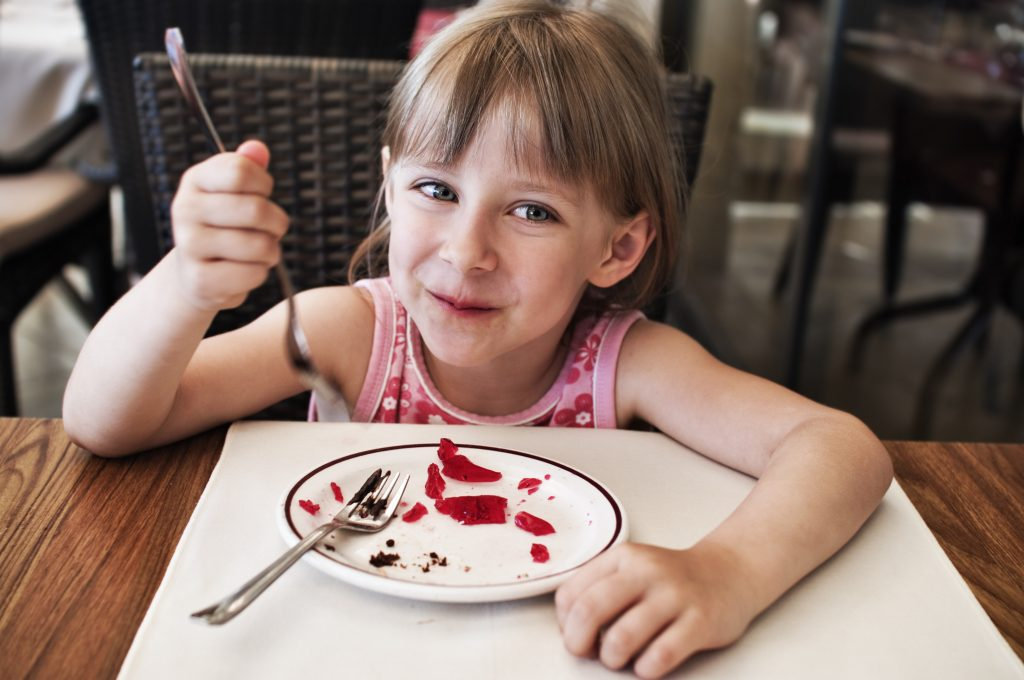 Little girl smiling, finishing her jelly-chocolate dessert.
