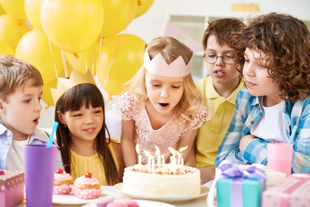 Little girl blowing out birthday candles surrounded by her friends