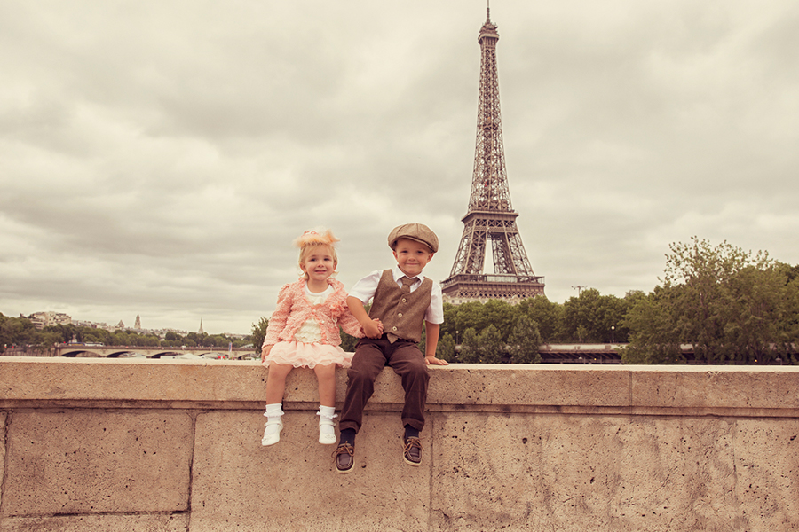 a boy and a girl sitting in front of the Eiffel Tower