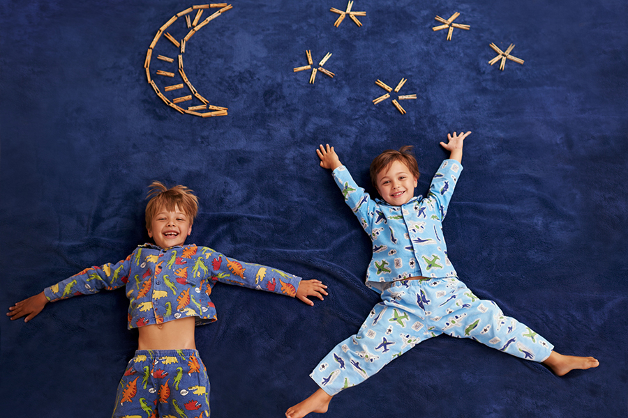 Two young boys in pjs lying under imaginary moon and stars