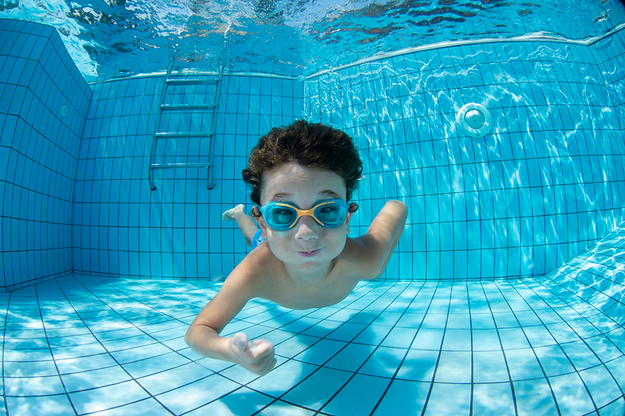 A boy swimming underwater in a pool