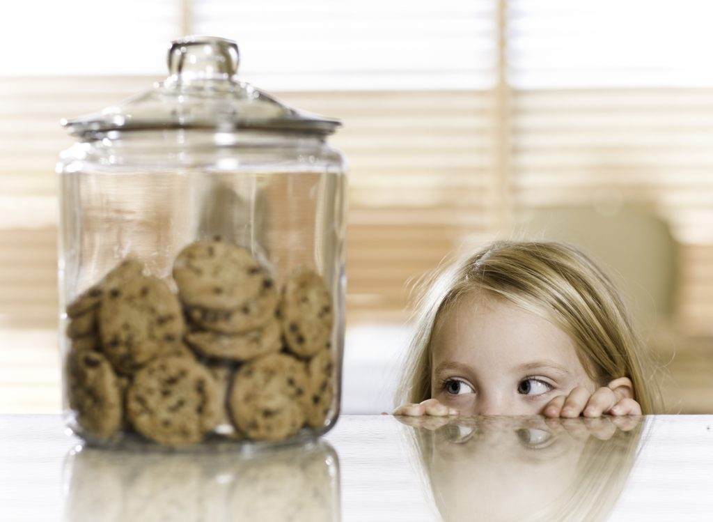 a little girl peeking over a counter at a cookie jar