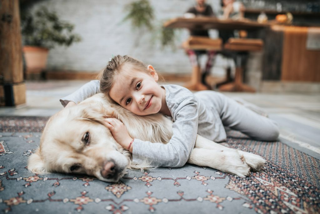Cute little girl relaxing with her dog on carpet at home and looking at camera.