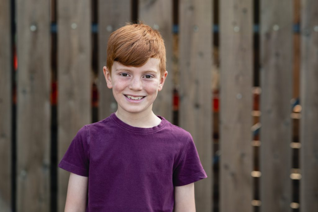A portrait of a boy smiling while looking at the camera.