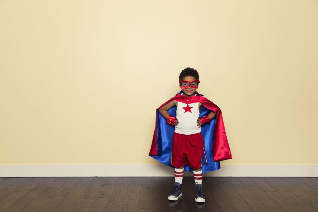 A young boy is dressed up as a superhero with a red cape, mask and shirt with a star on it. He stands ready to be brave and a hero with confidence against all challenges that may come his way. He is smiling at the camera and having fun.