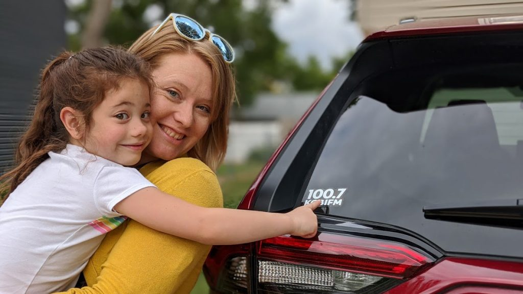 A mom and daughter standing next to a car