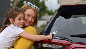 A mom and daughter standing next to a car with a KGBI Sticker