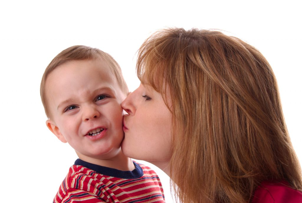 Mother kissing her son on the cheek and he is making a gross face. Isolated on a white background.