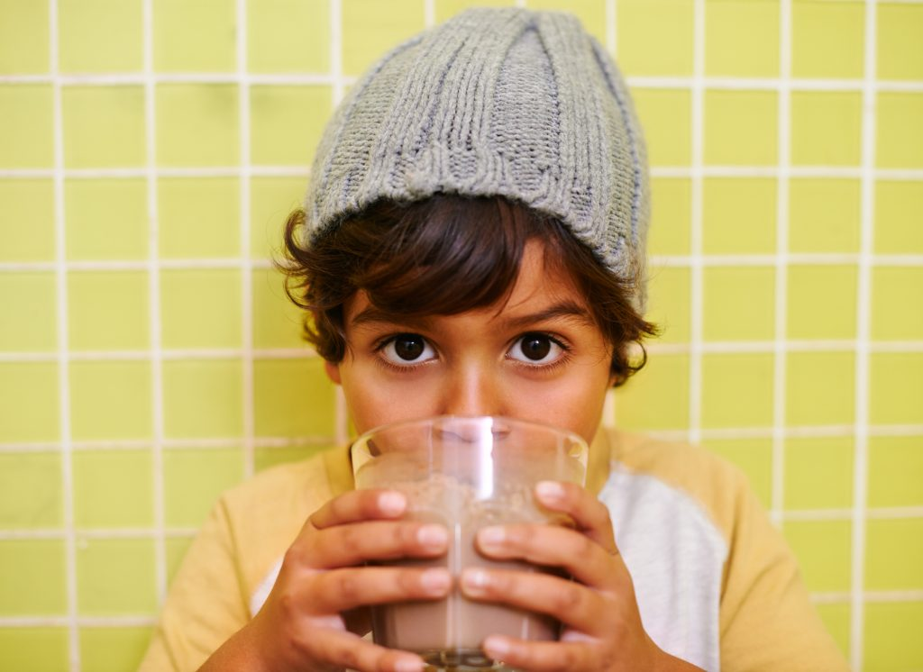 Shot of a cute little boy drinking a milkshake