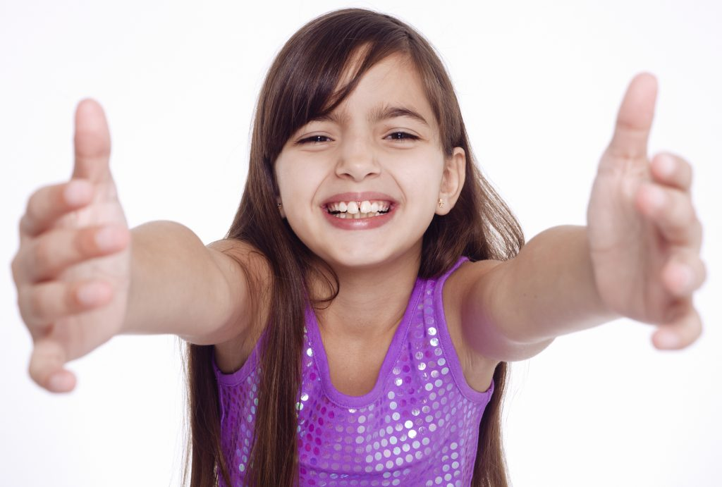Young girl aged 10 to 12 years holding out arms gesturing welcome, embrace, affection