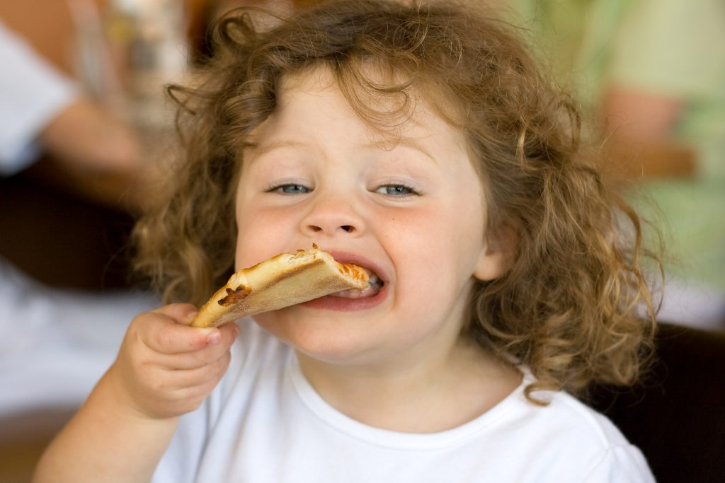Girl eating pizza in restaurant. Focus on slice of pizza.