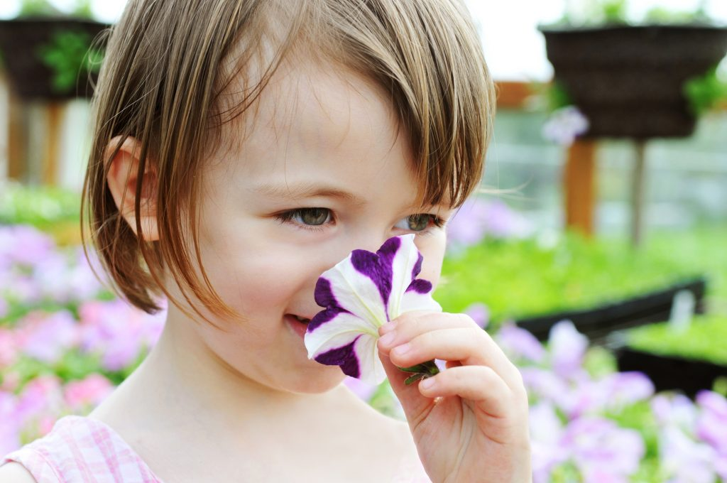 a girl smiling while smelling a petunia