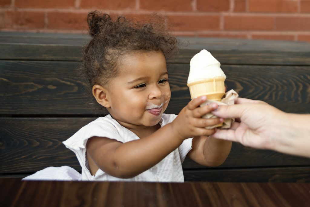 What better way to make a child happy than to offer them some ice cream? The expression of this adorable toddler tell it all. Hand of mother offering her 2 year's old daughter an ice cream cone. Horizontal indoors waist up shot with copy space.