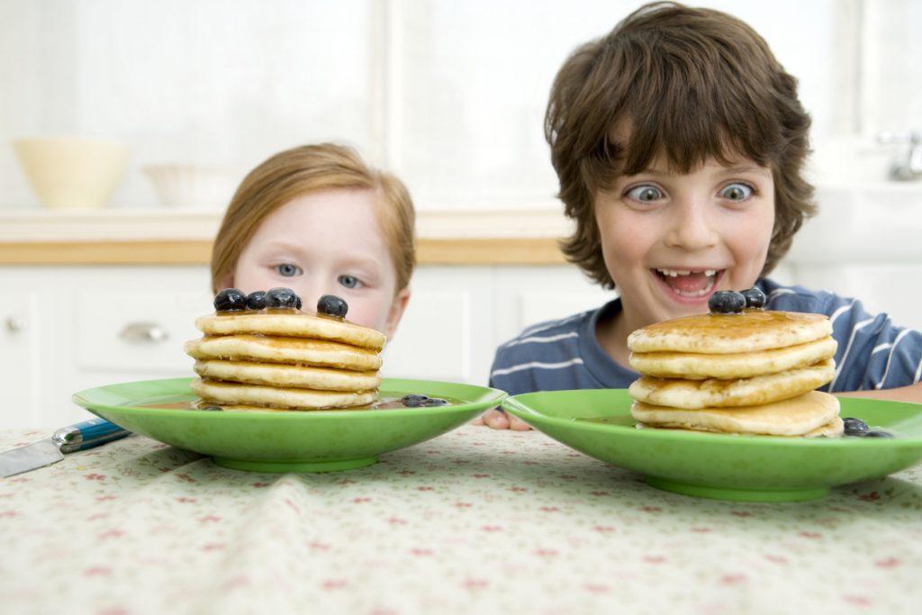 Boy and girl looking at pancakes