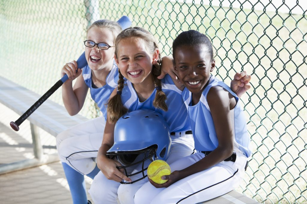 Multi-ethnic girls (9 years) on softball team at the ball park, sitting in dugout.