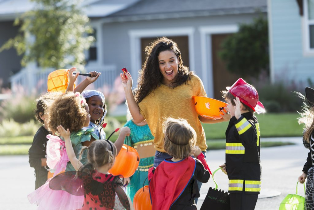 Hispanic woman (40s) giving out candy to multi-ethnic group of children (3-6 years) on halloween.