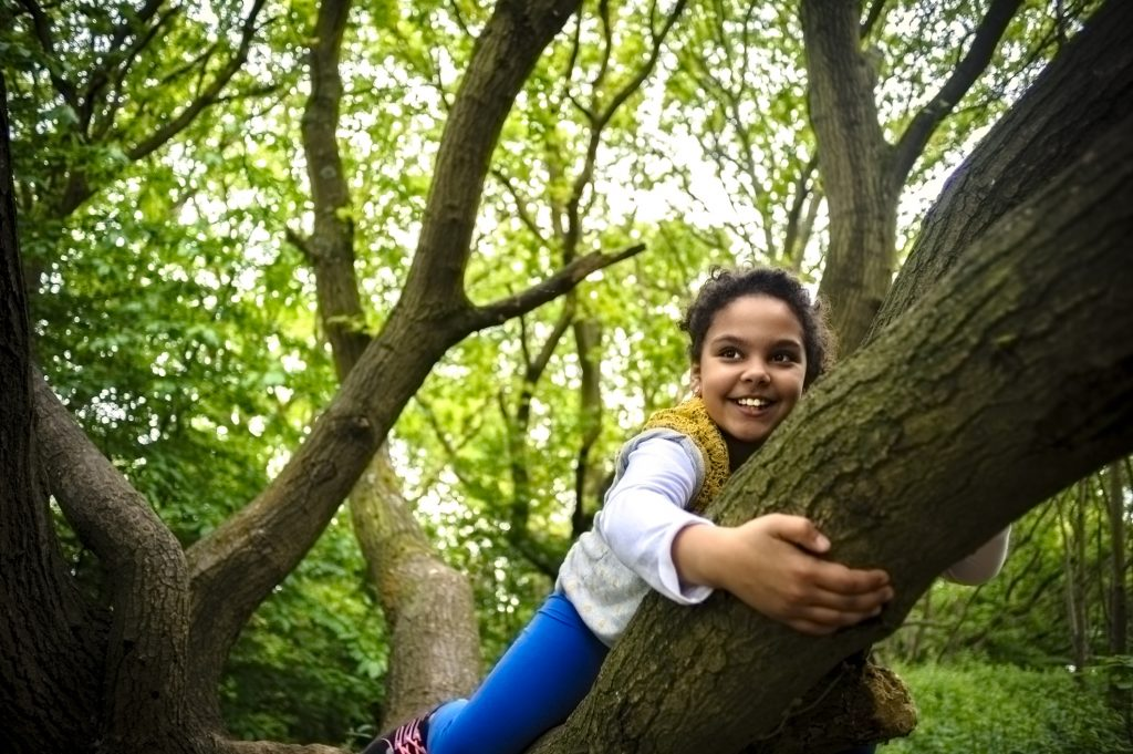 Stock photo of little girl aged 9 years old who is having fun by hanging on a tree. She is hanging on a thick branch. She is wearing blue legging and a grey top.