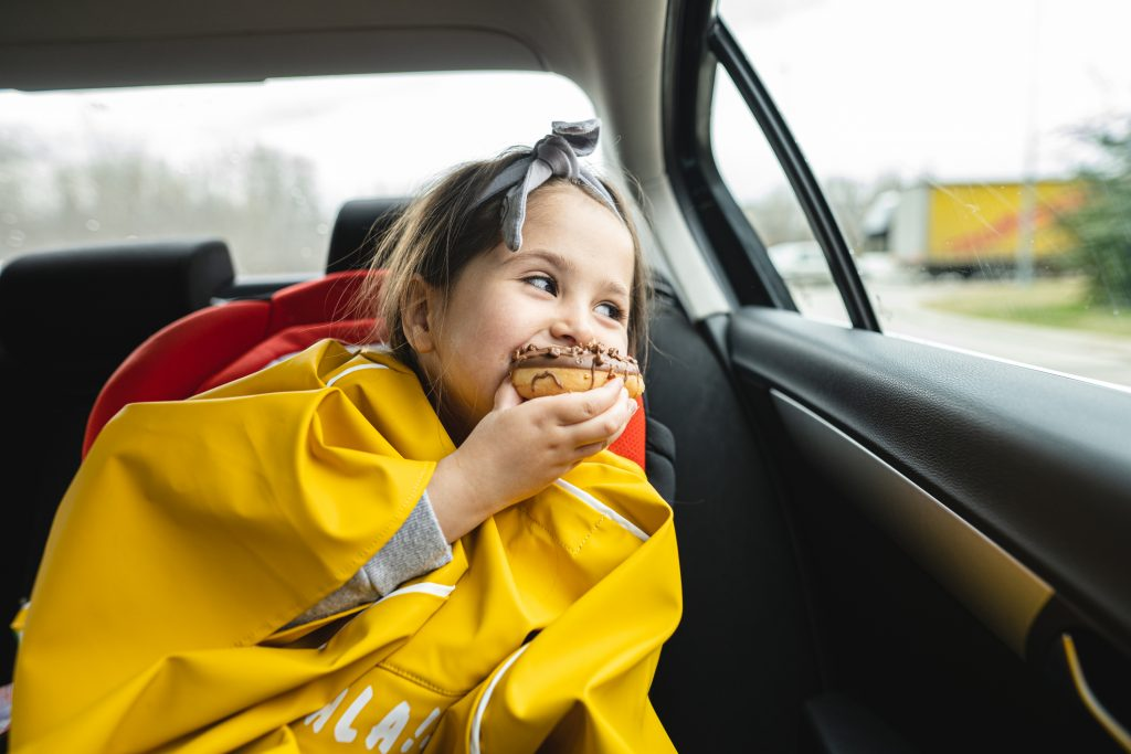 Cute innocent child enjoying a chocolate doughnut snack while riding on a back seat of a car during a road trip.