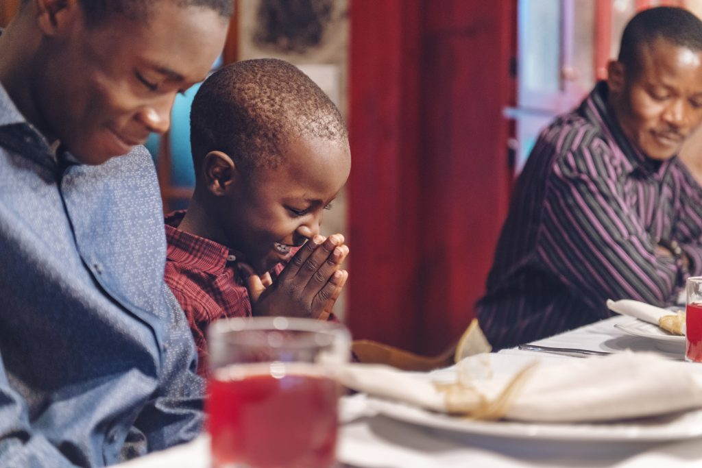 African-American doing a prayer during thanksgiving dinner