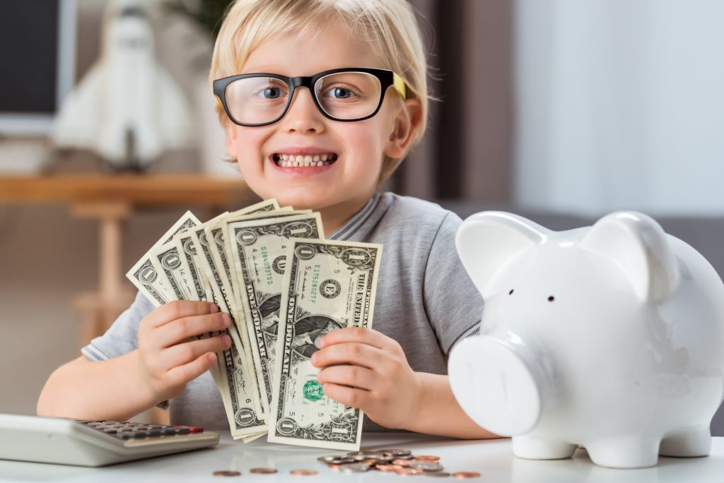 Little girl with piggy bank. Responsible investing concept.