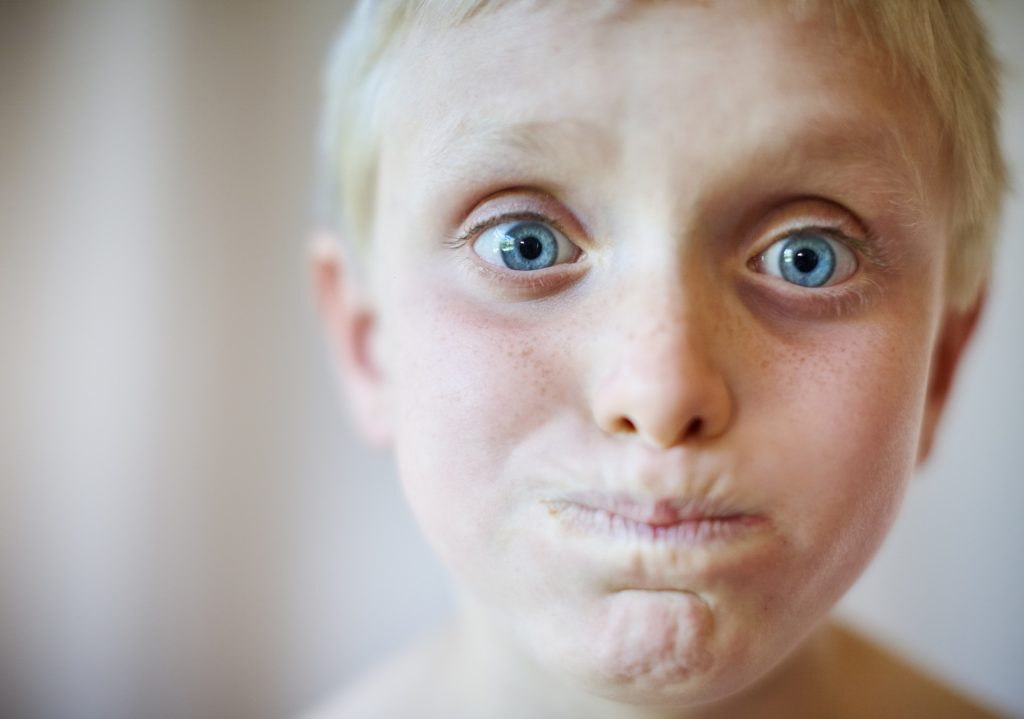 An 8 year old blond boy looks at camera, making a strange face and looking a bit panicky, perhaps with a very full mouth.