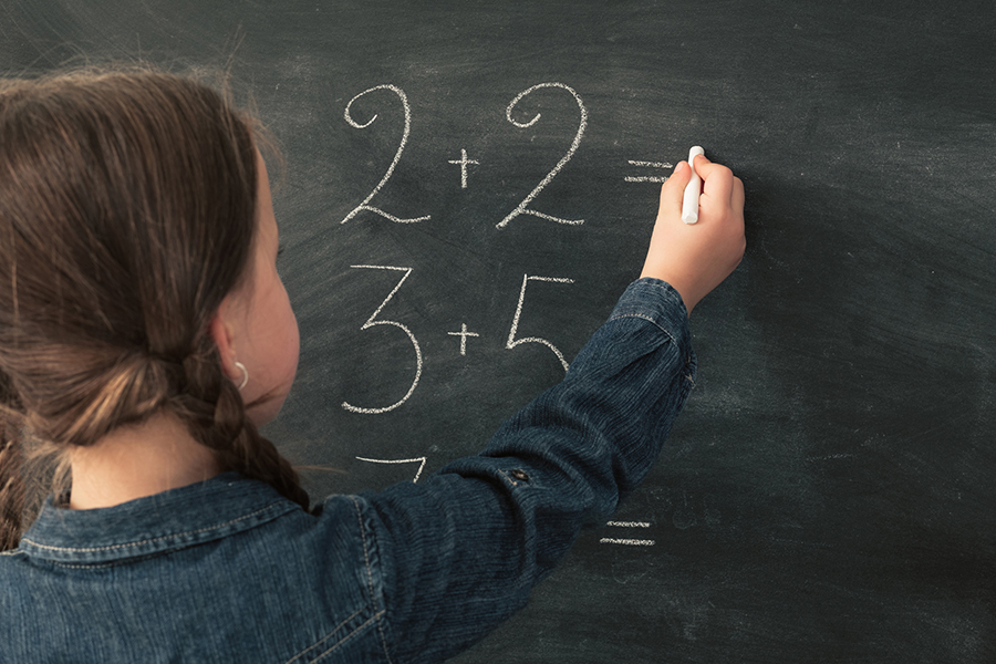 Primary school education. Back view of young girl doing math on chalkboard. Copy space.