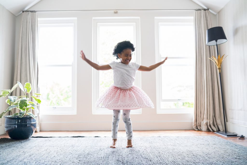 Full length of happy girl performing ballet dance at home. Female is wearing tutu while practicing. She is dancing against windows.