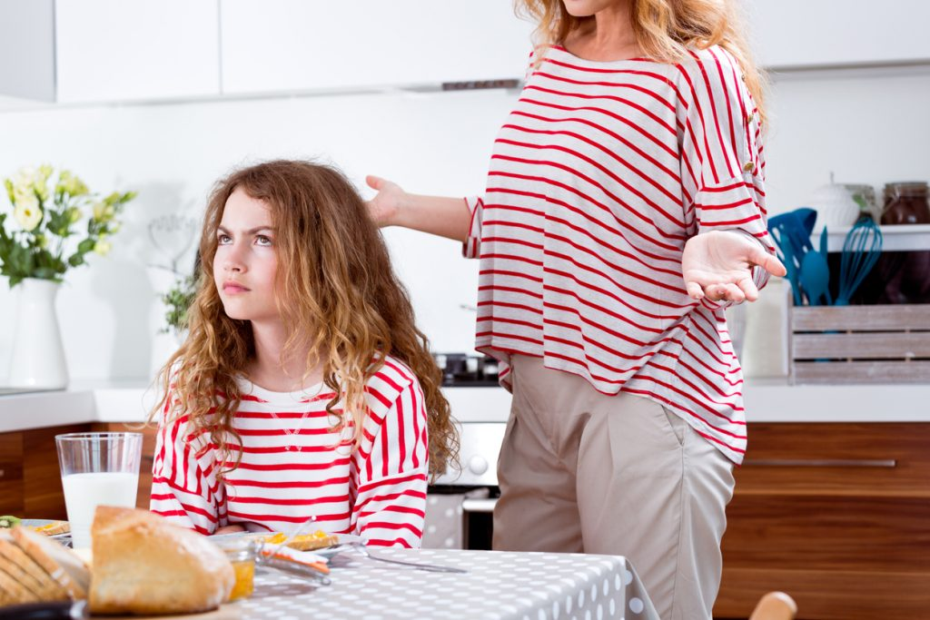 Offended teenager girl sitting at the breakfast table in the kitchen while upset mother standing behind her.