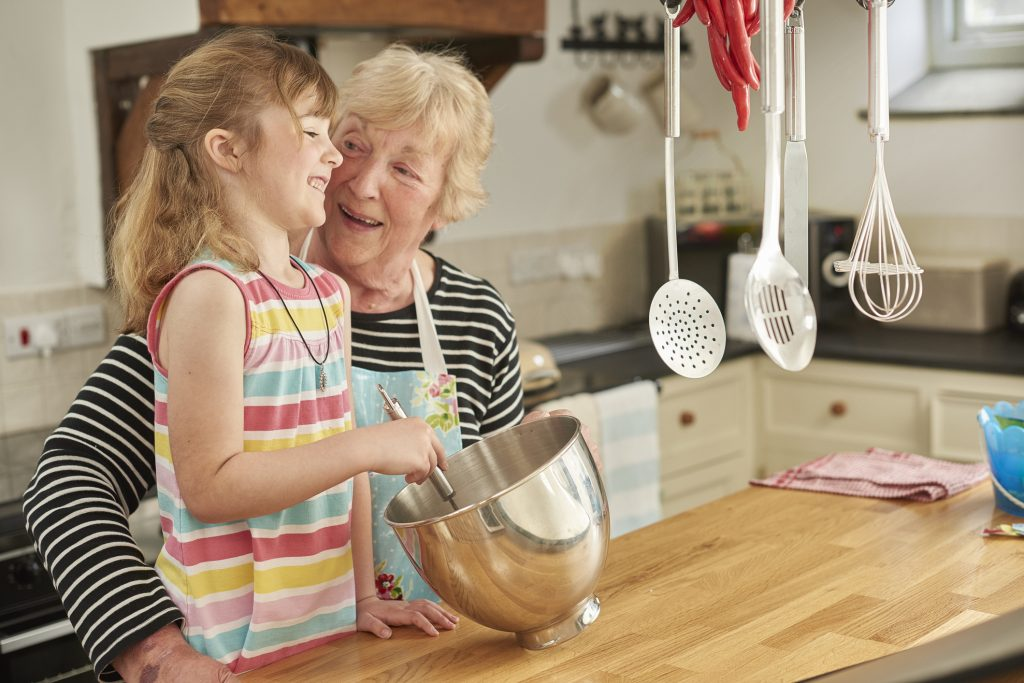 A little girl and her grandmother are in their kitchen as the little granddaughter whisks the eggs . Gran and little girl have a good laugh together .