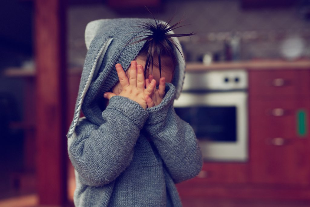 little girl covering face and playing hide and seek.