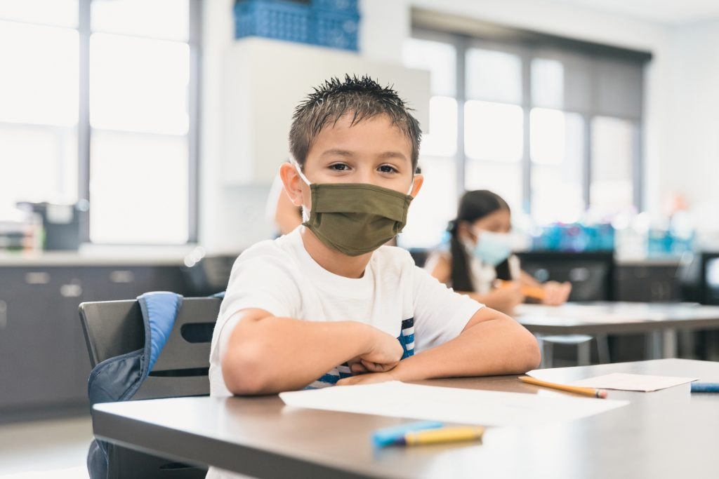 A cute elementary schoolboy looks at the camera while sitting at his desk. He is wearing a protective face mask and is socially distancing from other students during the coronavirus pandemic.