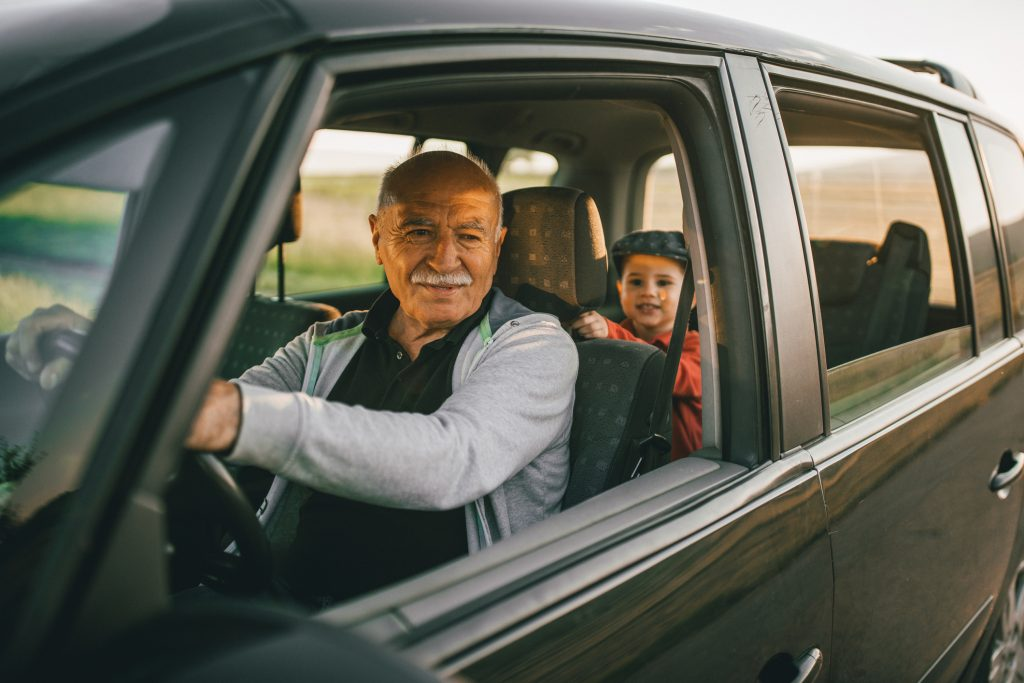 Grandfather and grandson having fun while traveling on the road trip